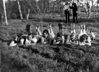 Sechs Frauen liegen auf dem Bauch