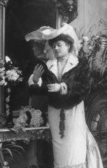 Frau mit Hut und Pelz betrachtet sich in Spiegel