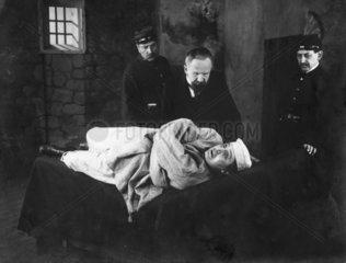 Mann liegt in Zwangsjacke auf einer Liege - Filmszene