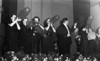 Frauen pusten auf der Buehne Luftballons auf