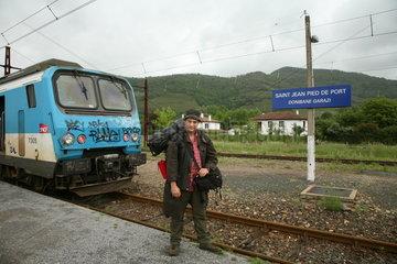 Mann auf Bahnhof beginnt Jakobsweg - Camino de Santiago