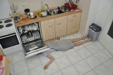 Frau liegt auf dem Kuechenboden