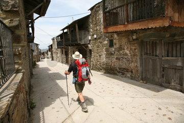 Pilger laeuft durch sehr alte Stadt am Jakobsweg - Camino de Santiago
