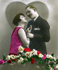 Paar laechelt sich an hinter Rosen