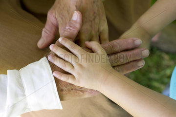 Child's hand holding elderly person's hand