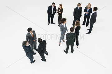 Business associates standing in small groups chatting
