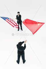 Men standing face to face  waving Chinese and American flags