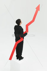 Businessman standing at top of steps holding arrow pointed upward