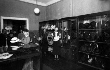mehrere Damen in einem Hutladen