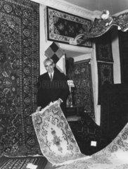 Teppichhaendler in seinem Laden praesentiert Teppich