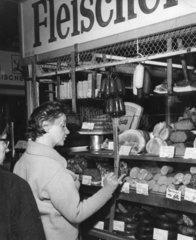 Frau bestellt Wurst in einer Fleischerei
