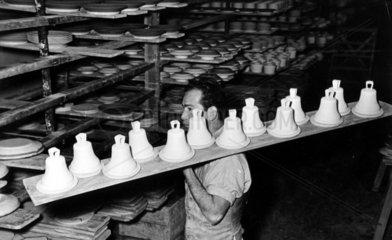 Mann transportiert Glocken aus Keramik zum Brennen