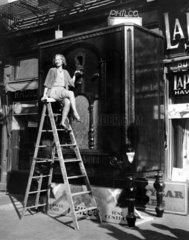 Frau sitzt auf Leiter vor Riesenschrank