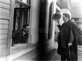 Mann begruesst Mann am Fenster