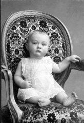 Baby sitzt in Sessel  1911