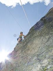 Schweiz  Frau klettert an einer Felswand