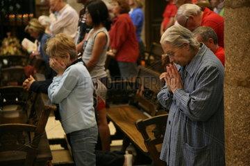 Menschen beten in einer Kirche auf dem Jakobsweg - Camino de Santiago