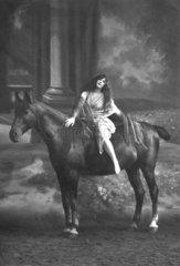 Frau in Tuch gehuellt sitzt auf Pferd