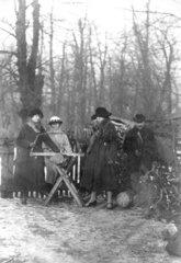Frauen und Mann beim Holzhacken und Saegen