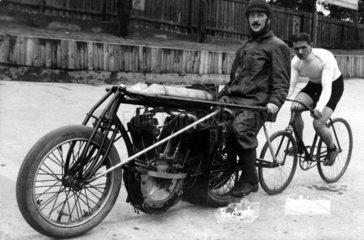 Fahrradfaher im Schlepptau eines Motorrades