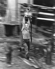 Junge haengt an Drahtseil