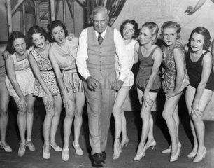 aelterer Herr mit einer Gruppe junger Taenzerinnen
