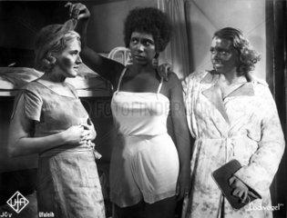 Schwarze Frau mit zwei schwarz geschminkten Frauen
