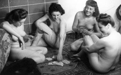 Vier nackte Frauen spielen Karten