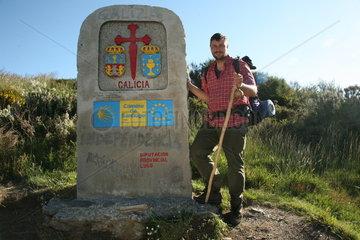 Pilger neben Eingangsschild der Provinz Galicien am Jakobsweg