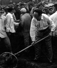 Mao Tse-tung grabt mit Schaufel