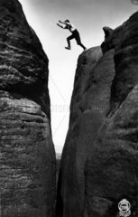 Mann springt ueber Felsspalt