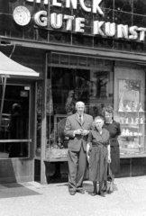 3 Leute stehen vor Kunstgeschaeft  1955