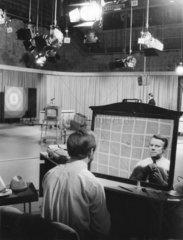 Fernsehmoderator richtet Krawatte im Spiegel vor Auftritt