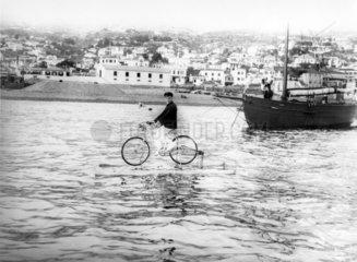 Mann fahrradfahrend auf Wasser