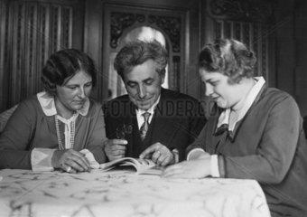 Mann und zwei Frauen lesen Zeitschrift