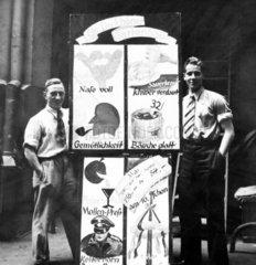 zwei Maenner posieren mit Werbetafeln
