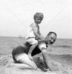 Sohn sitzt auf seinem Vater am Strand
