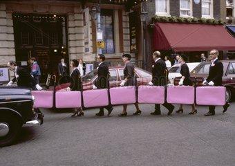 8 Personen mit pinken Koffern