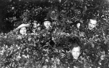 Vier Menschen verstecken sich in einem Busch