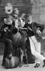Studenten einer Studentenverbindung singen mit Gesangsbuch neben Bierfaessern