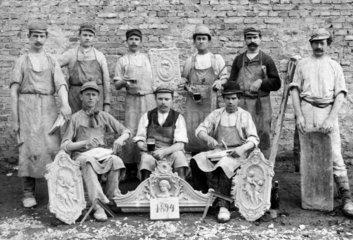 Neun Handwerker mit Stuckelementen vor Hauswand