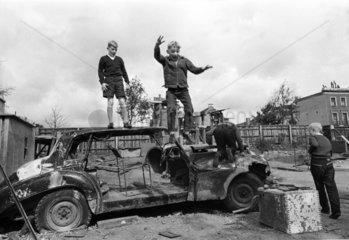 drei Kinder spielen mit Autowrack