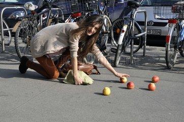 Frau hebt Aepfel vom Boden auf