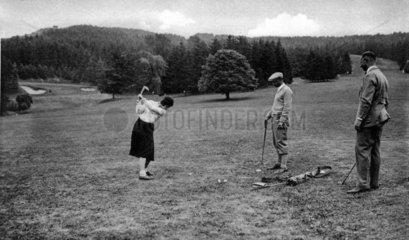 Frau und Maenner spielen Golf