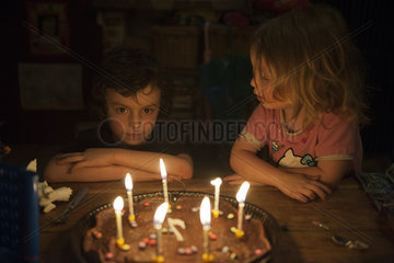 Little boy preparing to blow out candles on birthday cake as younger sister watches