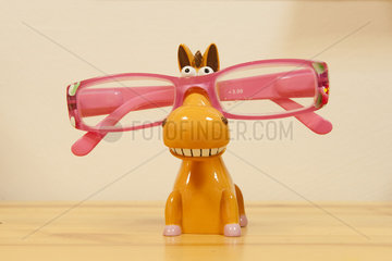 Glasses resting on toy horse
