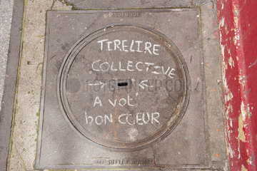 Manhole cover with writing in chalk saying piggy bank collection  have a good heart