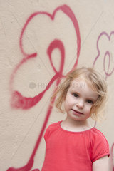 Little girl by wall with flower graffiti  portrait