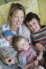 Mother sitting on hospital bed with children and newborn baby  portrait