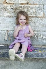 Little girl sitting on curb  portrait
